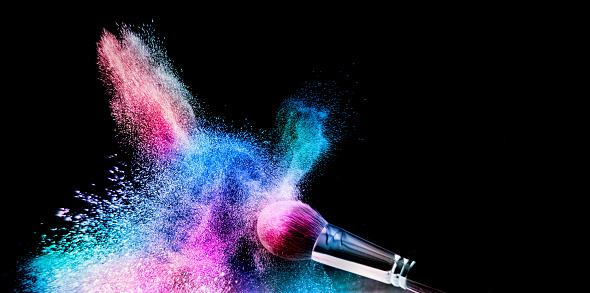 Image of a cosmetic powder brush, thrown in color loose powder, shot on black backgrownd.
