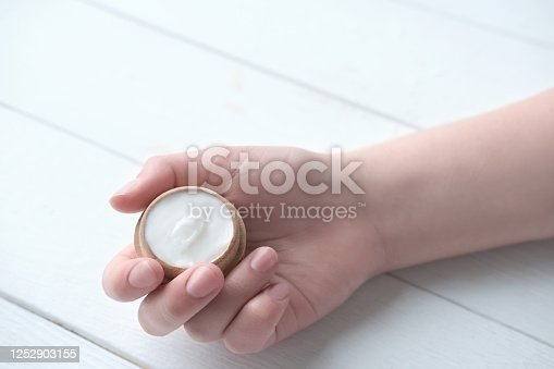 istock cosmetic product. collagen mockup. woman holding a wooden container with cream or serum for skin and hair. 1252903155