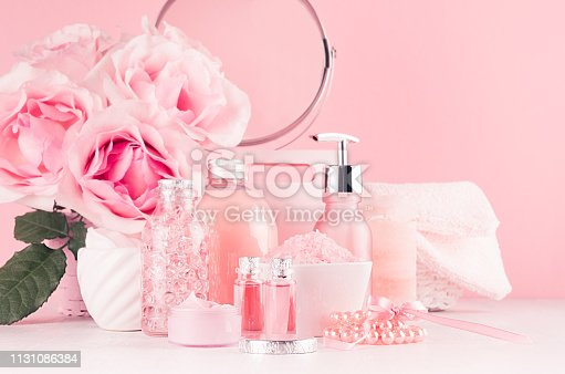 1056636898 istock photo Cosmetic products for aromatherapy, spa salon - essential rose oil, bath salt, cream, soap, bath accessories with round mirror, roses in pink color on white wood board. 1131086384