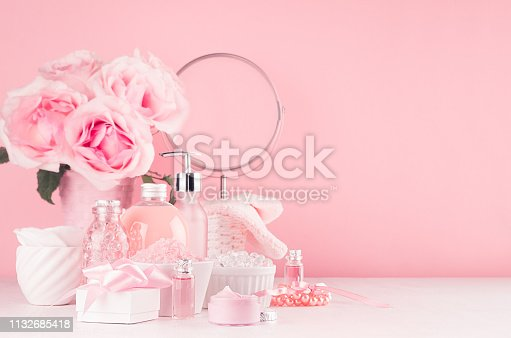 1056636898istockphoto Cosmetic products for aromatherapy, spa salon - essential rose oil, bath salt, cream, soap, bath accessories with round mirror, roses in pink color on white wood board. 1132685418