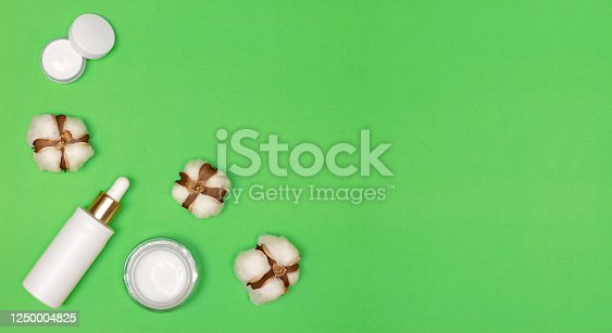 1128479585 istock photo Cosmetic serum, eye cream and face cream with white cotton flowers on green background. Top view, flat lay. Copy space. Natural facial cosmetics with cotton extract concept 1250004825