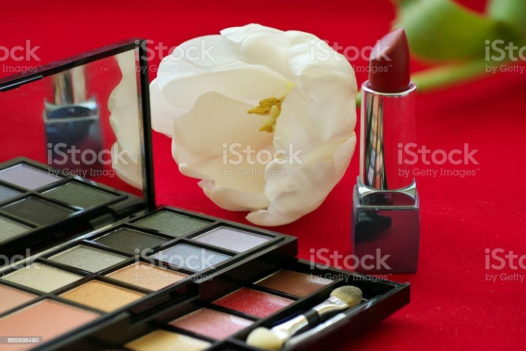 Cosmetic set lipstick eye shadow powder white tulip on red background foto stock royalty-free