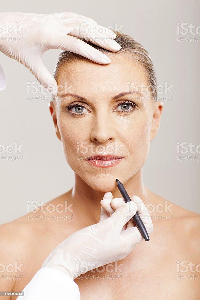 cosmetic surgeon marking mid age woman stock photo