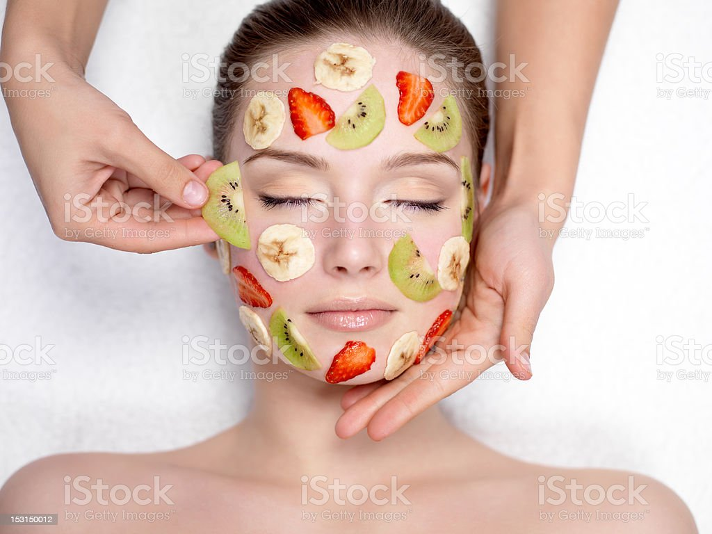 Cosmetician doing fruit mask on a face of  woman stock photo