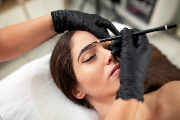 Cosmetician preparing to make a legit appearance of naturally full brows stock photo