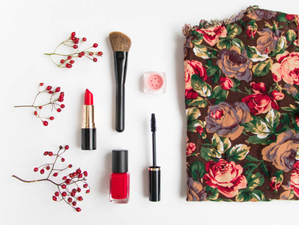 cosmetics and bright top on white. red colors flat lay - rotes oberteil stock-fotos und bilder