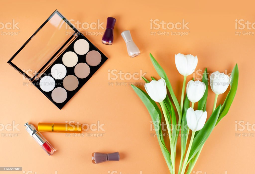 Cosmetics and flowers lies on a soft peach background. The contents...