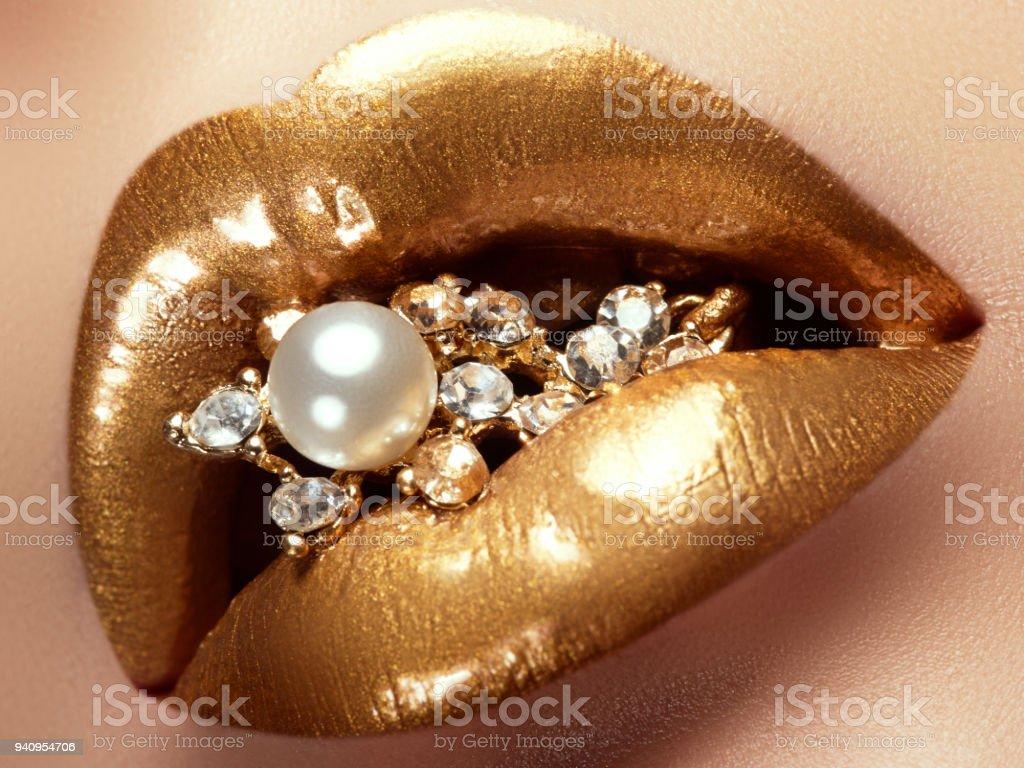 Cosméticos e make-up. Closeup de ouro lábios artísticos. Maquiagem de brilho labial brilhante. Fotos de uma menina linda com batom dourado e brilho. Lábios sexy e elegantes. Pérolas e diamantes na boca dela - foto de acervo