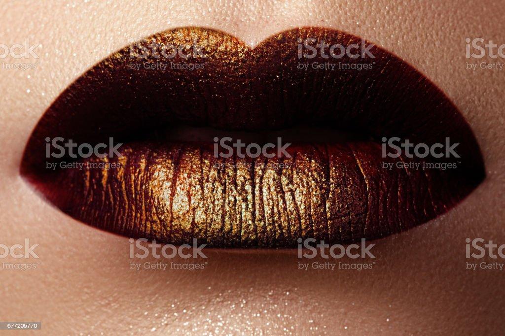 Cosméticos e make-up. Fotos de uma linda menina com lábio dourado - foto de acervo