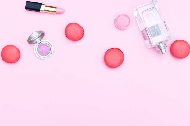 kosmetik und erdbeer makronen auf einem rosa hintergrund. textfreiraum - make up torte stock-fotos und bilder