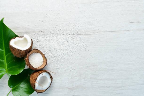 Cosméticos à base de coco e folhas tropicais. Em um fundo de madeira branca. Deitada plana. - foto de acervo