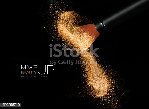 istock Cosmetics brush with glowing face powder. Dust explosion 520298710