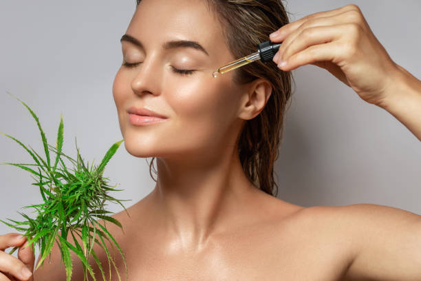 CBD cosmetics concept. Beautiful woman with a cannabis leaf stock photo