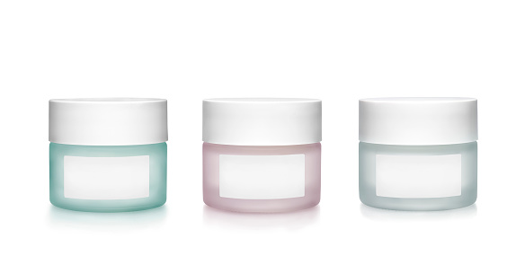 Three cosmetic containers of frosting glass. Green, pink and  grey color isolated on white background. Clipping path on containers and labels.