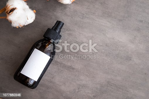 1042453716 istock photo Cosmetics in brown glass bottle with white label 1077880346