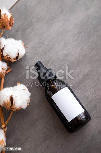 1042453716 istock photo Cosmetics in brown glass bottle with white label 1077880348