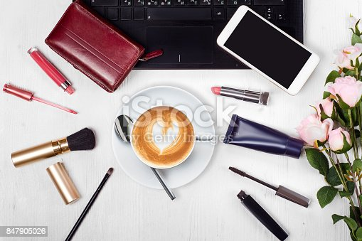 847905020 istock photo Cosmetics laptop cup of coffee cappuccino purse mobile phone smartphone flowers 847905026