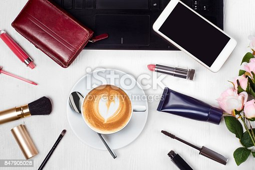 847905020 istock photo Cosmetics laptop cup of coffee cappuccino purse mobile phone smartphone flowers 847905028