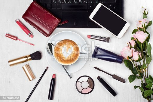 847905020 istock photo Cosmetics laptop cup of coffee cappuccino purse mobile phone smartphone flowers 847905038