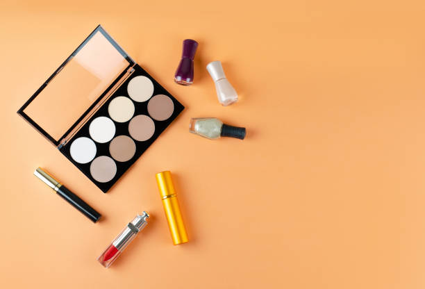 Cosmetics lies on a soft peach background. Contents of women's cosmetic bag stock photo