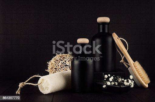 847096968 istock photo Cosmetics mock up -  blank black bottles, bath accessories, white flowers on dark wood board, copy space. 864357770