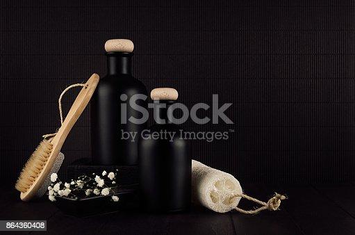847096968 istock photo Cosmetics mock up -  blank black bottles, bath accessories, white flowers on dark wood board, copy space. 864360408