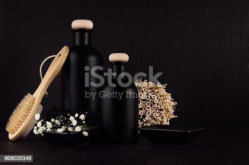 847096968 istock photo Cosmetics mock up -  blank black bottles, bath accessories, white flowers on dark wood board, copy space. 868005346