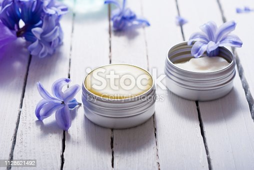 skin care product samples and purple hyacinth flowers on white wooden