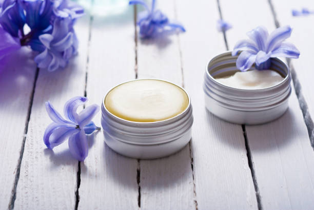 Cosmetics, moisturizer cream, purple flowers, white wooden tanle – zdjęcie