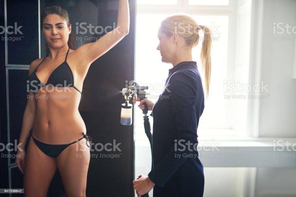 Cosmetics professional providing spraytan procedure to client stock photo