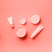 istock Cosmetics, skin care, beauty, body treatment concept. White cosmetic jar, tube, bottle and tropical monstera leaf over trendy coral color background. Top view. Flat lay. Mock-up. 1160028203