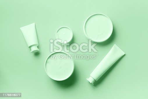 istock Cosmetics, skin care, beauty, body treatment concept. White cosmetic jar, tube, bottle and tropical monstera leaf over trendy mint color background. Top view. Flat lay. Mock-up. 1176618077
