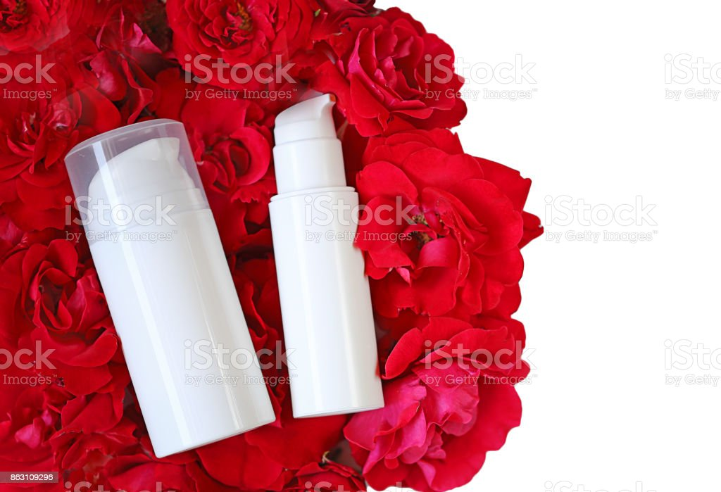 Cosmetics & Skin Care Mocap. cream and serum with rose extract in white cosmetic bottles on red rose petals isolated on white background. Organic Cosmetics Concept stock photo