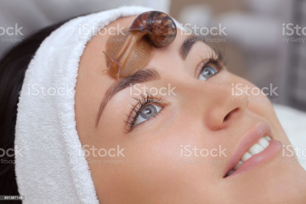 Cosmetological procedure. Beautiful young woman with a snail ahatin on her face stock photo
