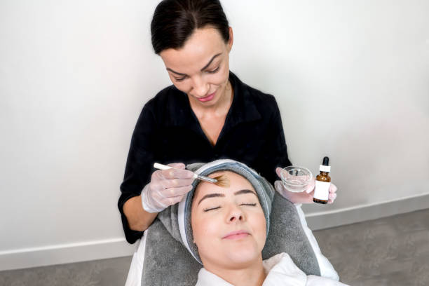 cosmetologist administering chemical peel treatment on patient in a beauty spa, for skin rejuvenation, complexion and acne beauty treatments. two females in a clinical spa. - chemical peel stock pictures, royalty-free photos & images