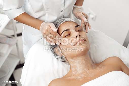 Cosmetologist applying cream on female face in cosmetology salon