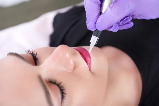 kosmetikerin anwendung permanent make-up auf lippen auf schöne junge mädchen - gesicht make up anleitungen stock-fotos und bilder