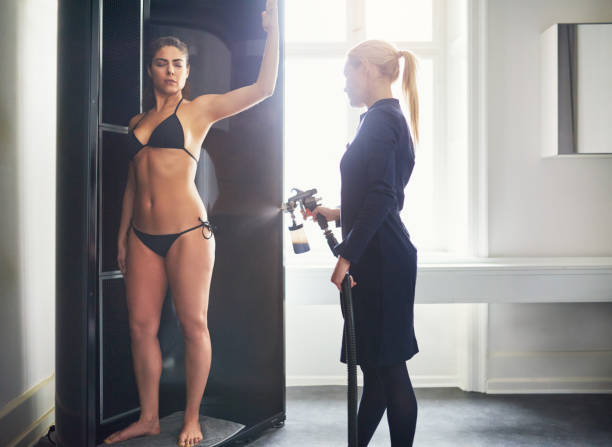 Cosmetologist applying spray tan on woman in salon stock photo
