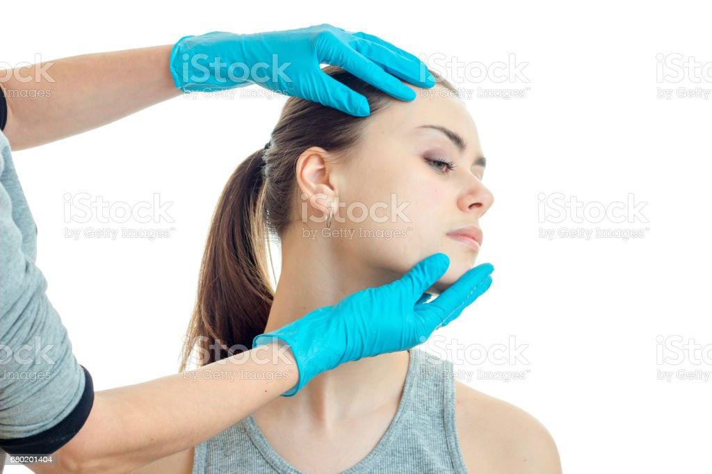 cosmetologist checks hands in gloves face of a young woman stock photo