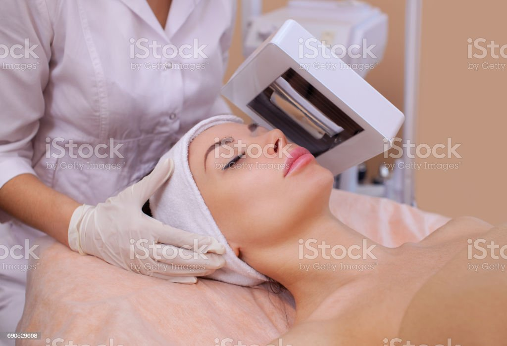 Cosmetologist diagnose with wood's lamp skin disease, and also reveals inflamed areas on the face stock photo