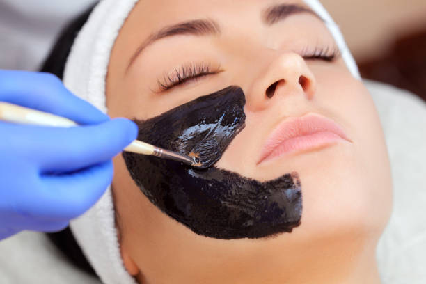 Cosmetologist does a black mask to cleanse the skin and anti-wrinkle on the face of a beautiful woman, spa treatments and cosmetology concept. Cosmetologist does a black mask to cleanse the skin and anti-wrinkle on the face of a beautiful woman, spa treatments and cosmetology concept. dark spots face stock pictures, royalty-free photos & images