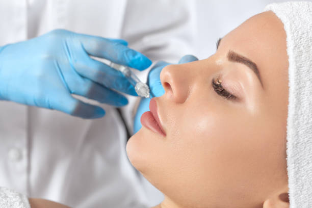 Cosmetologist does anti wrinkle injections on the chin, lips and on the face of a beautiful woman in a beauty salon. Cosmetology concept.Cosmetologist does anti wrinkle injections on the chin, lips and on the face of a beautiful woman in a beauty salon. C stock photo