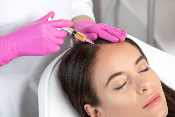Cosmetologist does prp therapy against hair loss and anti-dandruff of a beautiful woman in a beauty salon. Cosmetology concept. stock photo