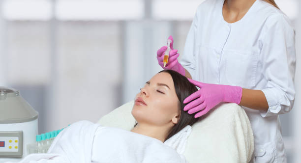 Cosmetologist does prp therapy against hair loss of a beautiful woman in a beauty salon. Treatment of problem skin cosmetology concept. stock photo