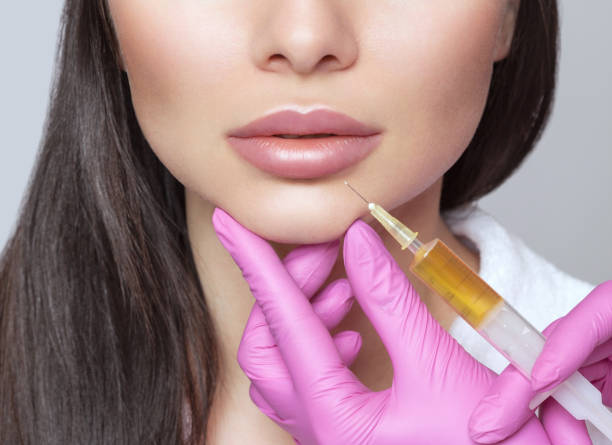 Cosmetologist does prp therapy anti wrinkle and aging skin on the chin and on the face of a beautiful woman in a beauty salon. Cosmetology concept. stock photo