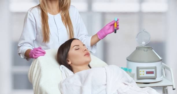 Cosmetologist does prp therapy on the face and scalp of a beautiful, young woman with clean skin in a beauty salon. There is in vitro  blood plasma, ready for injection. Cosmetology concept. stock photo