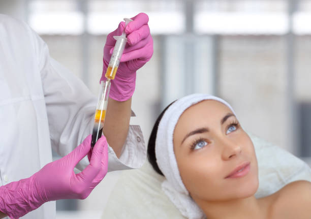 Cosmetologist does prp therapy on the face of a beautiful woman in a beauty salon. There is in vitro  blood plasma, ready for injection. Cosmetology concept. stock photo
