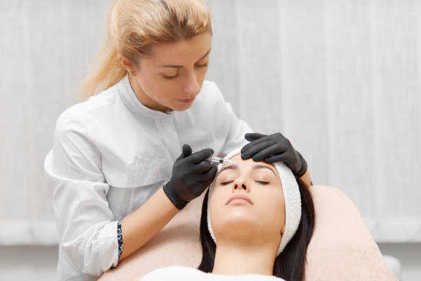Cosmetologist doing beauty procedure for patient stock photo