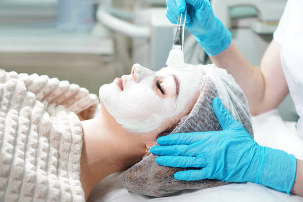 cosmetologist doing cosmetic face mask treatment for the young woman. - chemical peel stock pictures, royalty-free photos & images
