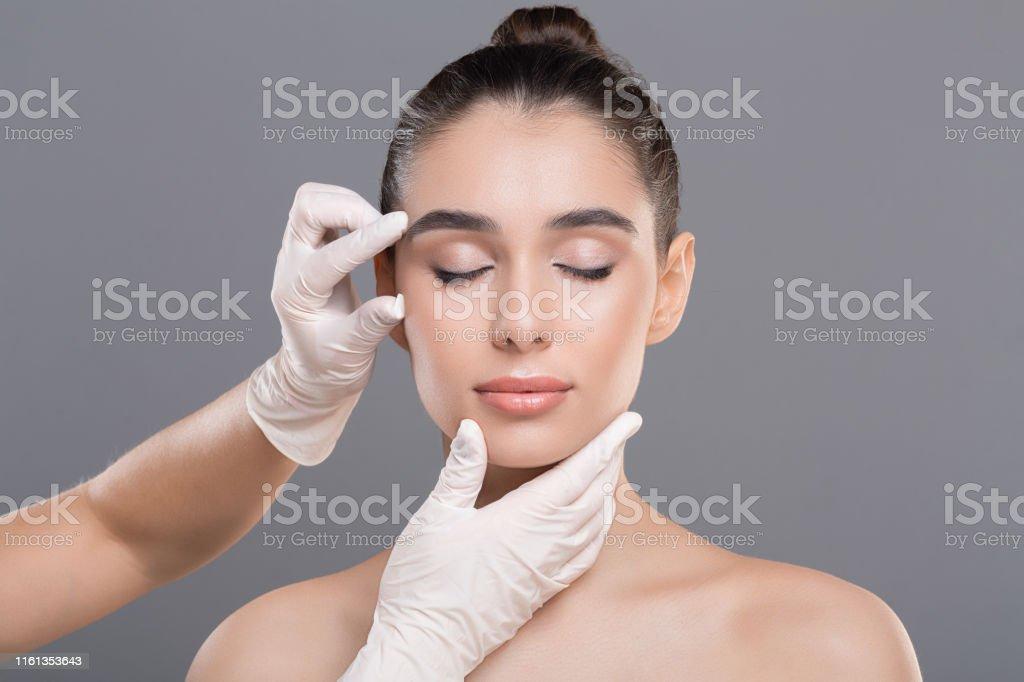 Kosmetologe untersucht Gesichtsfalten auf junge Minundgesicht - Lizenzfrei Alternative Behandlungsmethode Stock-Foto